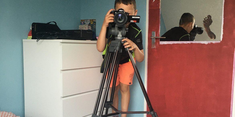 Boy behind a tripod taking a photo