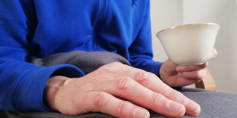Oude hand met kopje