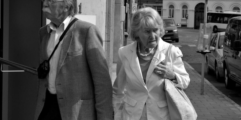 Twee oude mensen lopen hand in hand over straat