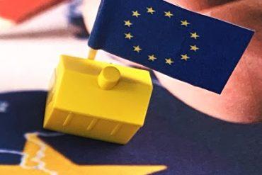 Europese vlag achter geel Monopoly-huisje op een ingezoomde wereldkaart