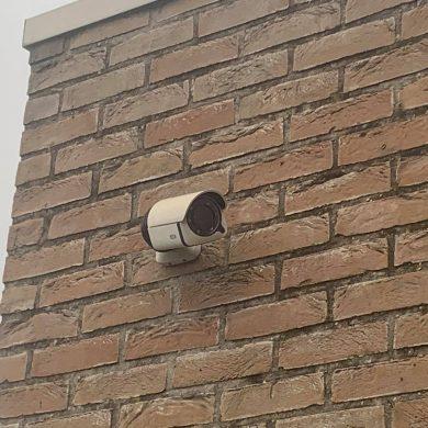 een camera hangt aan een bakstenen muur
