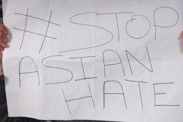 Twee handen houden een papier vast waar #StopAsianHate op staat